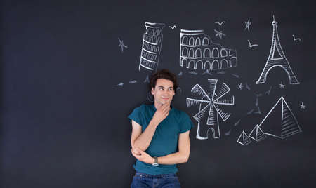 ilustrations: Young man playing with a draw that shows the world attractions. Large copy space on left.