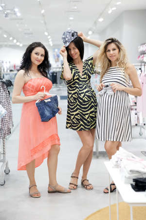 some: Lovely young pregnant women looking for some baby clothes in a store for their new babies.