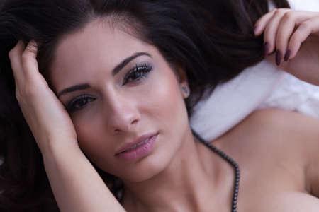 nude female body model: Portrait of a sexy brunette posing in a bedroom. Stock Photo