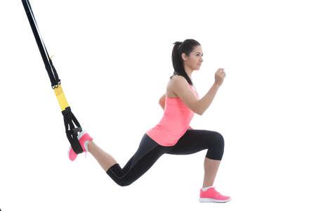 muskeltraining: Athletic Frau mit funktionellen Schleifen für das Training auf weißem Hintergrund.