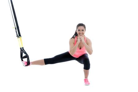 Atletische vrouw met functionele lussen voor de opleiding op een witte achtergrond. Stockfoto