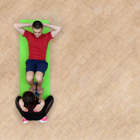 laying abs exercise: Fitness couple doing abs exercises on mat. Above image with copy space. Stock Photo