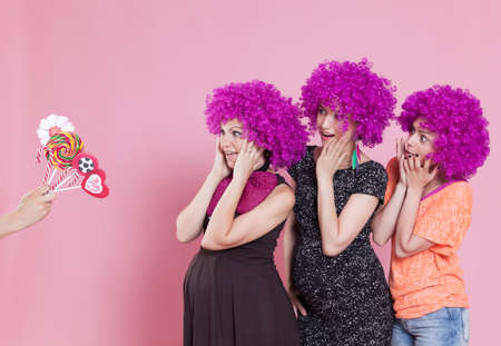 wigs: Portrait of a young women wearing a carnival wigs and surprised by some candy offer. Stock Photo