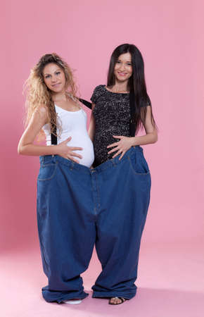 pregnant jeans: Portrait of a young pregnant women wearing a very large jeans Conceptual image about weight loss themes. Stock Photo