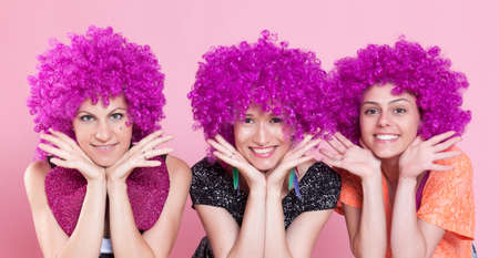 wigs: Portrait of a young women wearing a carnival wigs over a pink background. Stock Photo