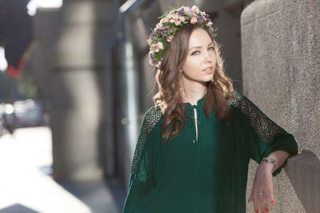 circlet: Young lovely woman with a nice flower circlet posing against sun flare.