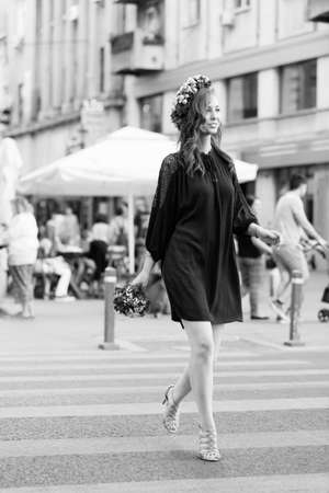 circlet: Young lovely woman with a nice flower circlet crossing the street smiling and feeling attractive. Black and white image with grain added as effect.