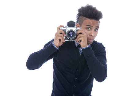he old: Young african man holding an old camera peeking on what he sees. Stock Photo