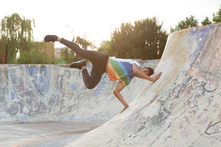 somersault: African american young man posing at sunset in a skate park.