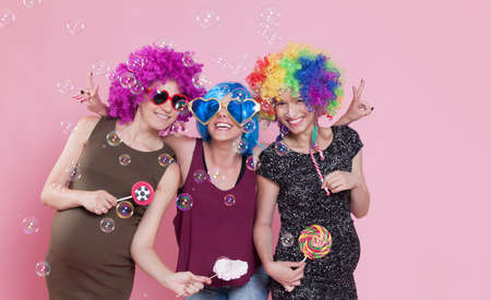 disguised: Group of young women disguised for a party, with candies, ballons and wigs.