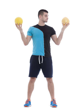 indecisive: Fit man holding a pomelo in one hand and a sport ball in the other hand Stock Photo