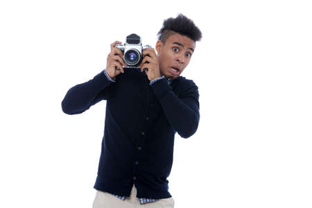he old: Young african man holding an old camera and being very shocked on what he sees.