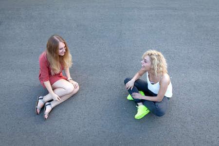 sidewalk talk: Happy girls sitting on sidewalk having a chat.