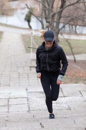upstairs: Joyful woman running upstairs in the park on rainy day.