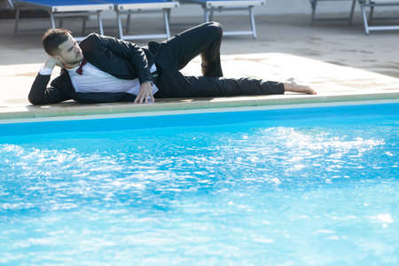 Man sitting by the pool, wearing black suit feeling sad and dissapointed.