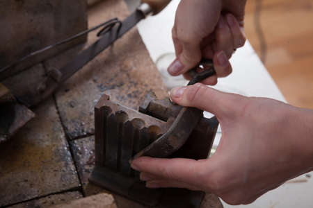 crucible: Jeweler at work, crafting in a jewelery workshop.