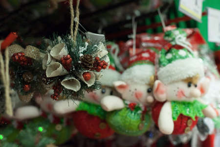 Christmas tree decorations hanging on a shelf for sale in a shop.