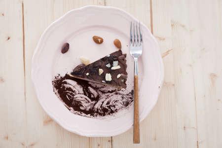 プレーンテキストビーガンのスライスは、それを食べる準備ができて白い皿の上のケーキを冷笑します。 写真素材