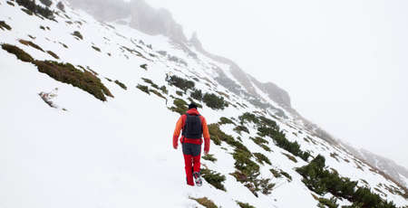 he: A man is walking alone on a moutain hike. The weather seems so cold and the wind is strong but he must keep going through the snow.