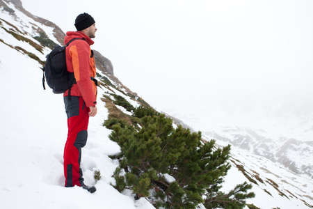 A young man on the top of snowy mountains is having a realxing moment. He is admiring the breathtaking view and also releasing stress. Stock Photo