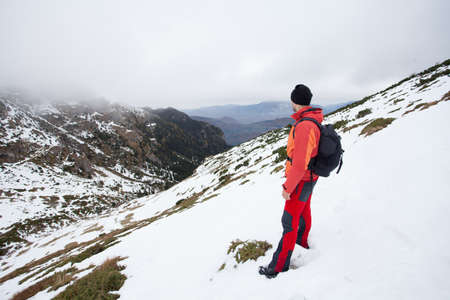 he: A man reached the top of the snowy Carphatians mountains and now he is admiring the beautiful silence and beauty of the mountains. Stock Photo