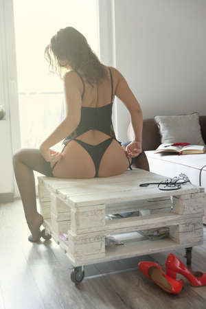 Sexy lady touching herself softly on a table.