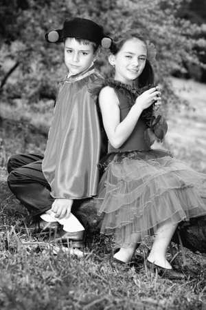 Portrait of a very young couple in spanish style garment having fun in a meadow.