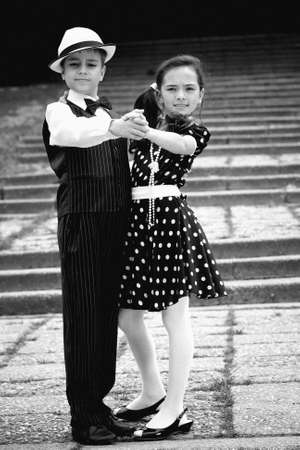 Portrait of a very young couple in retro garment posing at the camera.