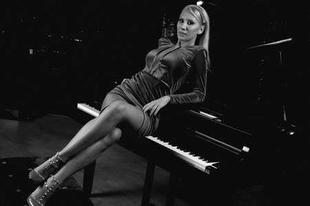Sensual woman posing and playing at a piano instrument. Standard-Bild