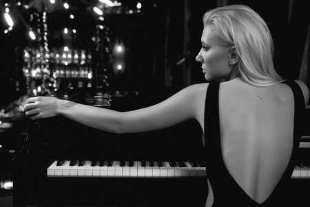 Sensual woman posing and playing at a piano instrument. Archivio Fotografico