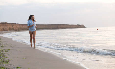 Gorgeous young woman enjoying the quality time with herself at the seaside and beach surroundings.