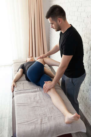 Young woman getting massage seesion at home by a physiotherapist.