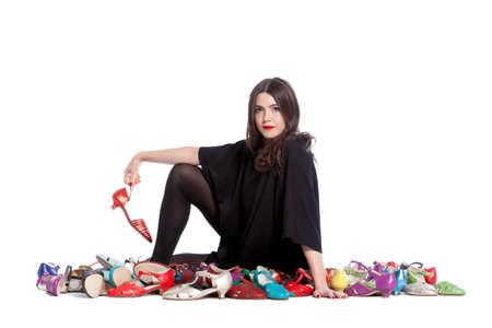 Young woman isolated on white background having a lot of shoes with many sizes and colors. Archivio Fotografico