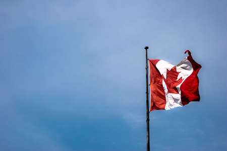 Canada flag against blue sky with copy-space