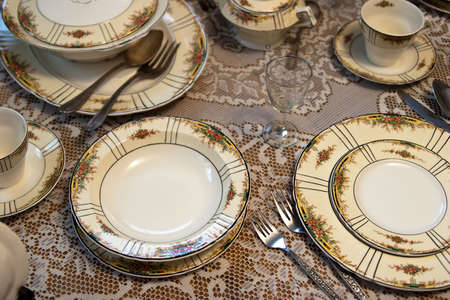 Antique dinner place setting on table photo