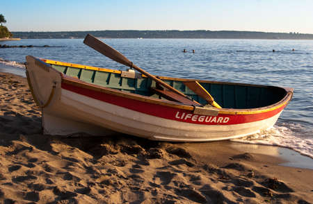Empty lifeguard rowboat on beach at sunset Stock Photo