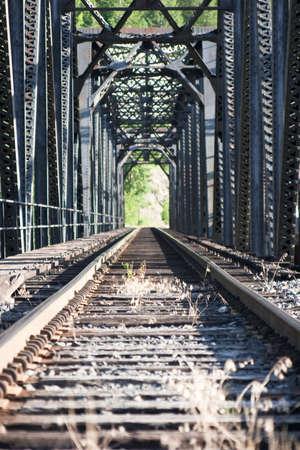 Staring down railroad tracks across bridge Stock Photo