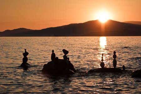 Freestanding rock sculptures in ocean at sunset Stock Photo
