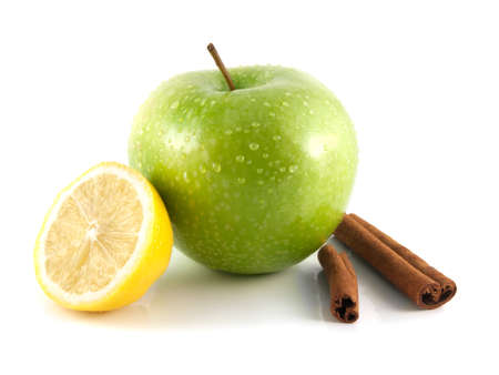 Isolated wet green apple and lemon with cinnamon pods (white background). Fresh diet fruit (water drops). Healthy fruit with vitamins.