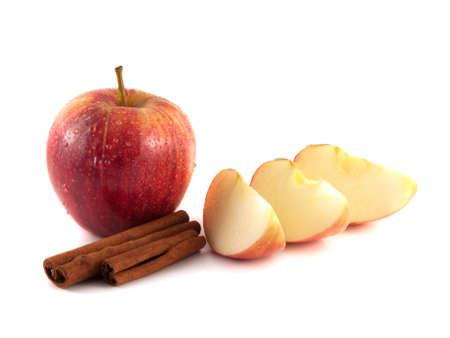 Isolated wet red apple with three slices and cinnamon pods on a white background. Fresh diet fruit. Healthy fruit with vitamins. photo