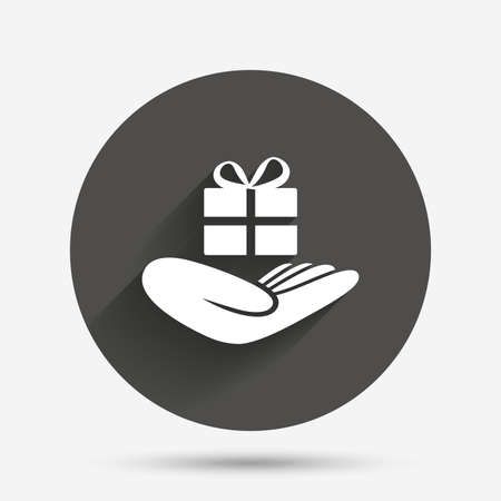 give a gift: Give a gift sign icon. Hand holds present box with bow. Circle flat button with shadow. Vector