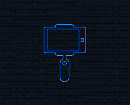 Neon light. Monopod selfie stick icon. Self portrait tool. Glowing graphic design. Brick wall. Vector Illustration
