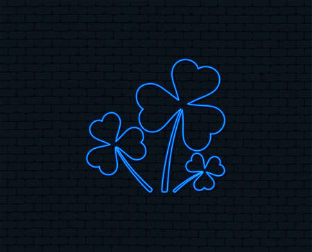 Neon light. Clovers with three leaves sign icon. Saint Patrick trefoil shamrock symbol. Glowing graphic design. Brick wall. Illustration