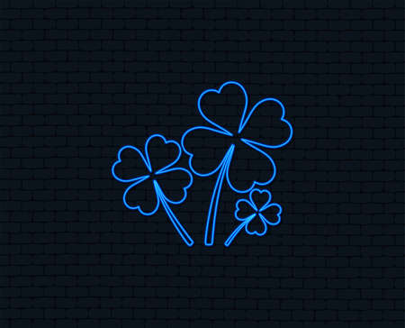 Neon light. Clovers with four leaves sign icon. Saint Patrick symbol. Glowing graphic design. Brick wall.