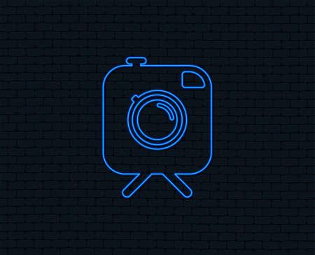 Neon light. Hipster photo camera sign icon. Retro camera on tripod symbol. Glowing graphic design. Brick wall. Vector Illustration