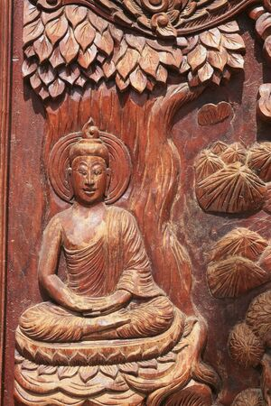 Buddha carving on wooden temple door photo