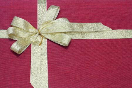 Background: gold ribbon with bow on red canvas texture photo