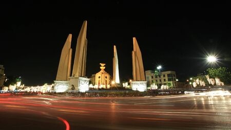 Background: night scene of democracy monument in Bangkok, Thailand