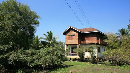 Rural background: traditional wooden thai house with natural environment