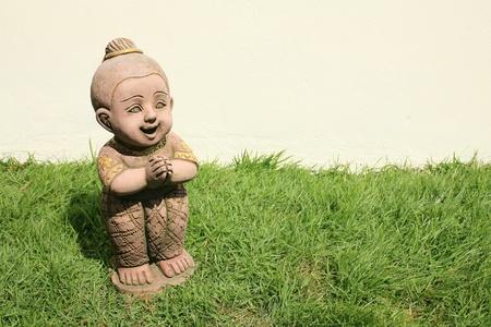 thai boy: Ornament: traditional thai boy statue salute on the grass field
